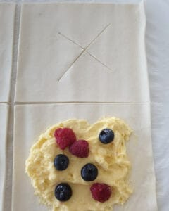 Blätterteig Rechtecke mit Pudding bestrichen und mit Beeren belegt.