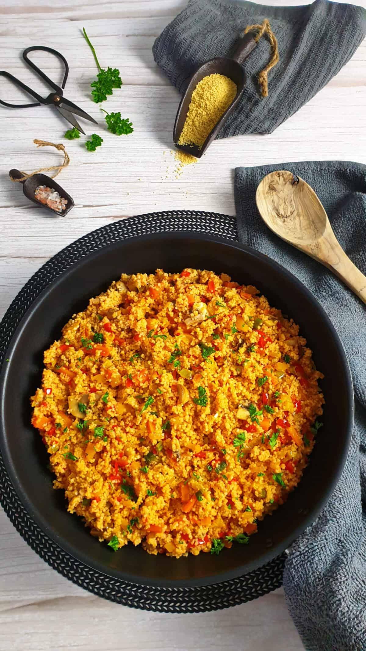 In einer Pfanne eine vegetarische Couscous Pfanne mit Gemüse, bestreut mit Petersilie. Im Hintergrund Deko,