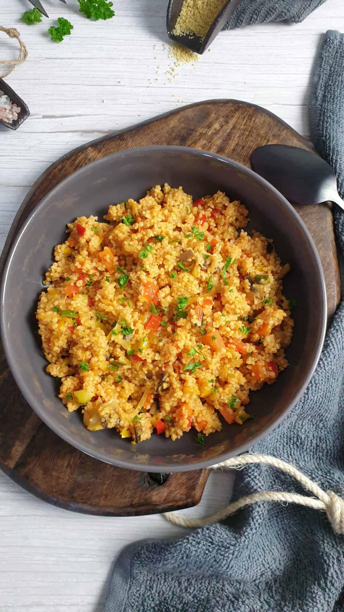 In einer grauen Schale angerichtet Couscous Gemüse Pfanne mit Petersilie bestreut. Im Hintergrund Deko.