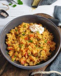 In einer grauen Schale angerichtet Couscous Gemüse Pfanne mit einem Joghurt Dip. Im Hintergrund Deko.