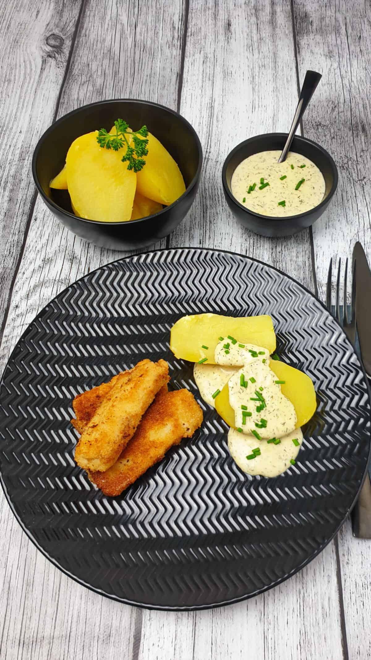 Auf einem braunen Teller 3 selbst gemachte Fischstäbchen mit Kartoffeln und Dill-Senf-Soße. Im Hintergrund Deko.