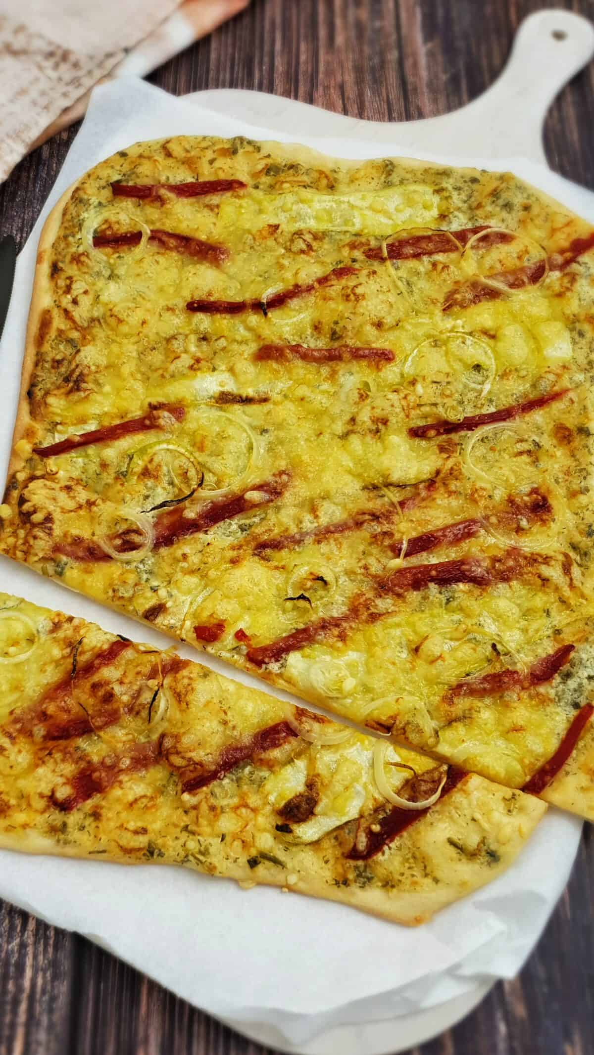 Flammkuchen vegetarisch mit gerösteter Paprika angerichtet auf einem hellen Flammkuchen-Brett mit Backpapier.