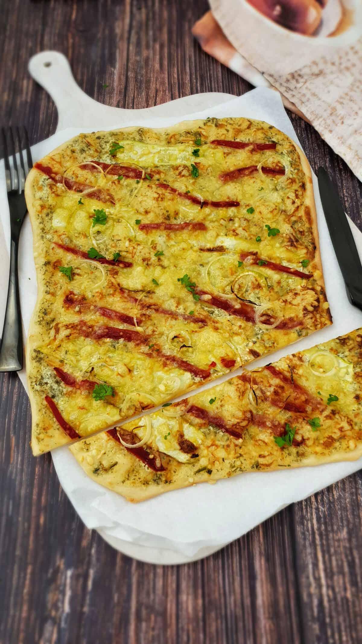 Vegetarischer Flammkuchen mit gerösteter Paprika angerichtet auf einem hellen Flammkuchen-Brett mit Backpapier.