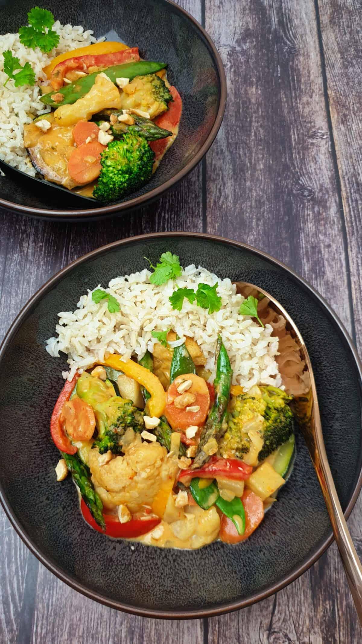 Gemüse Curry mit Blumenkohl und Brokkoli in einer grauen Schale mit Reis serviert.