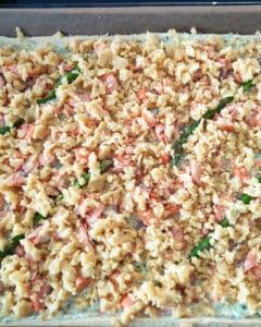 Ein Hefeteig belegt mit Lachs, Spargel und Parmesan Streusel.