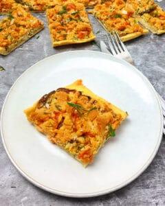 Auf einem weißen Teller ein Stück Lachs-Kuchen mit Parmesan Streuseln. Im Hintergrund Deko.