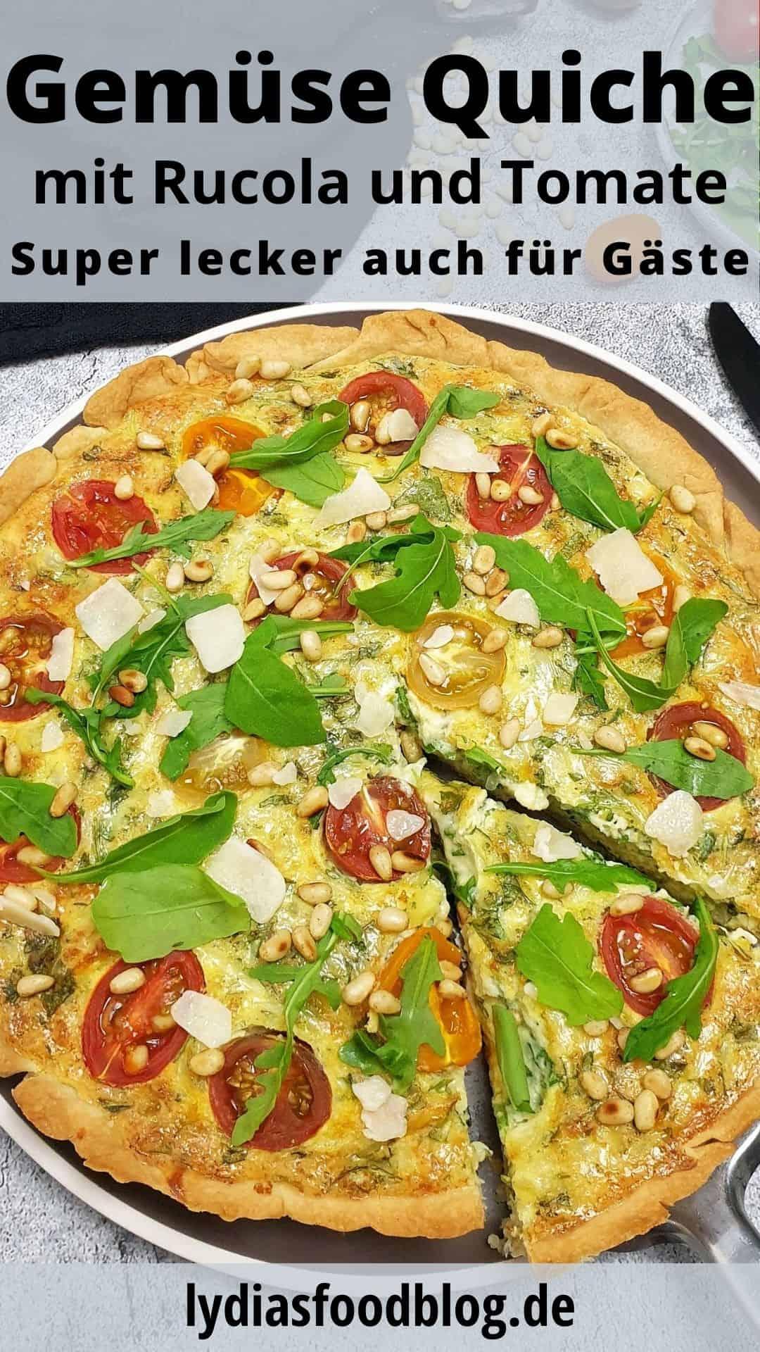 Auf einem graubraunen Teller eine Quiche mit Rucol, Tomaten und Pinienkernen. Mit Parmesan bestreut. Im Hintergrund Deko.