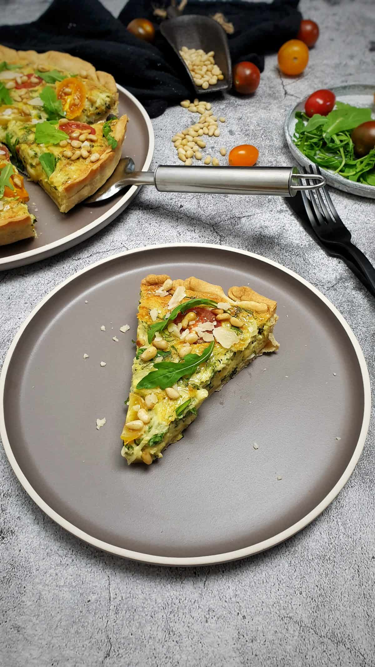 Auf einem graubraunen Teller ein Stück Quiche mit Rucol, Tomaten und Pinienkernen. Mit Parmesan bestreut. Im Hintergrund Deko.