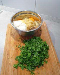 Auf einem Schneidebrett klein geschnittener Rucola und eine Schale mit Eiern, Käse und Crème fraîche.
