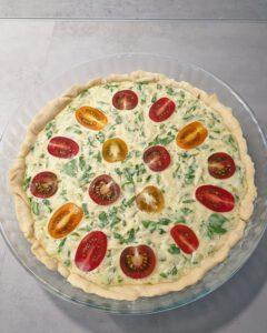 In einer runden Form eine Quiche mit bunten Tomaten.