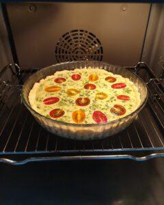Eine Tomaten-Quiche mit Rucola im Backofen.