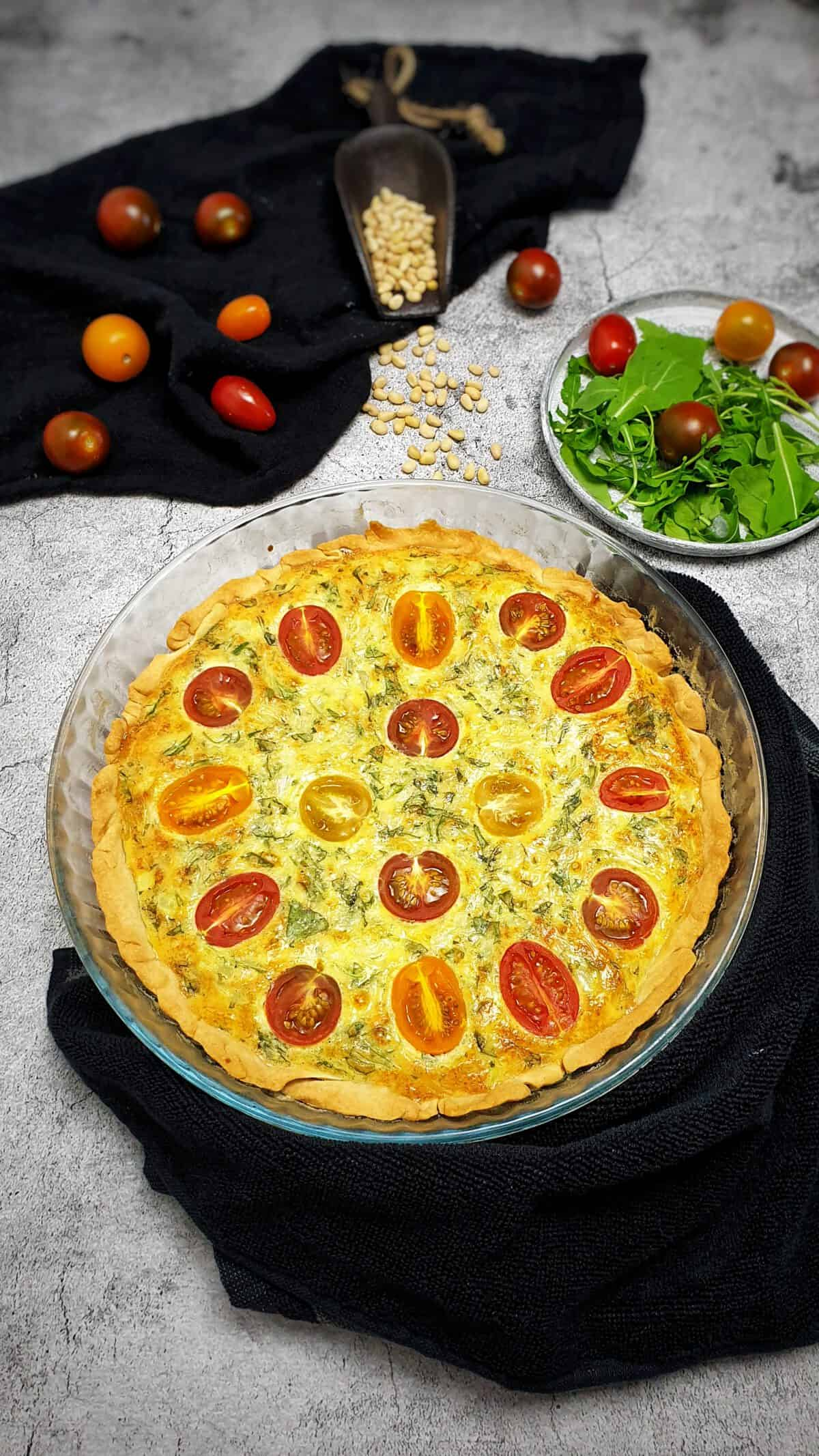 Auf einem graubraunen Teller eine Rucola-Quiche mit Tomaten. Im Hintergrund Deko.