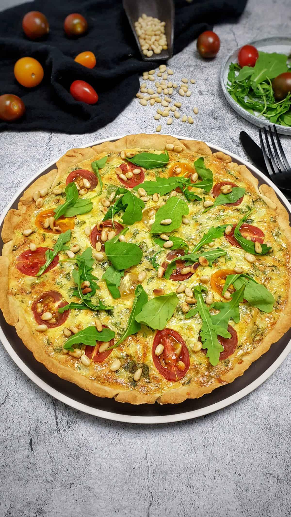 Auf einem graubraunen Teller eine Quiche mit Rucol, Tomaten und Pinienkernen. Im Hintergrund Deko.