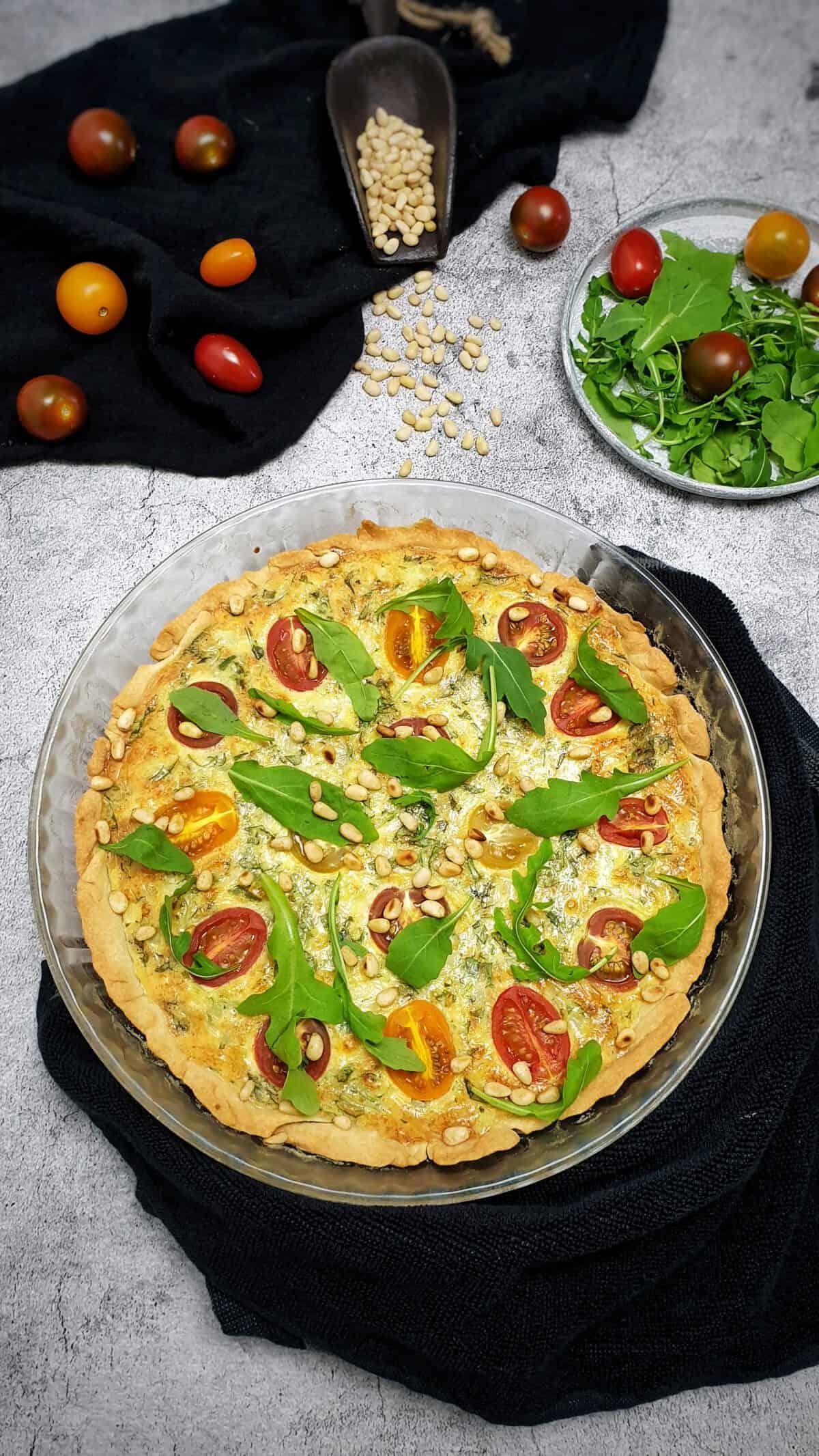 Auf einem graubraunen Teller eine Rucola-Quiche mit Tomaten und Pinienkernen. Im Hintergrund Deko.