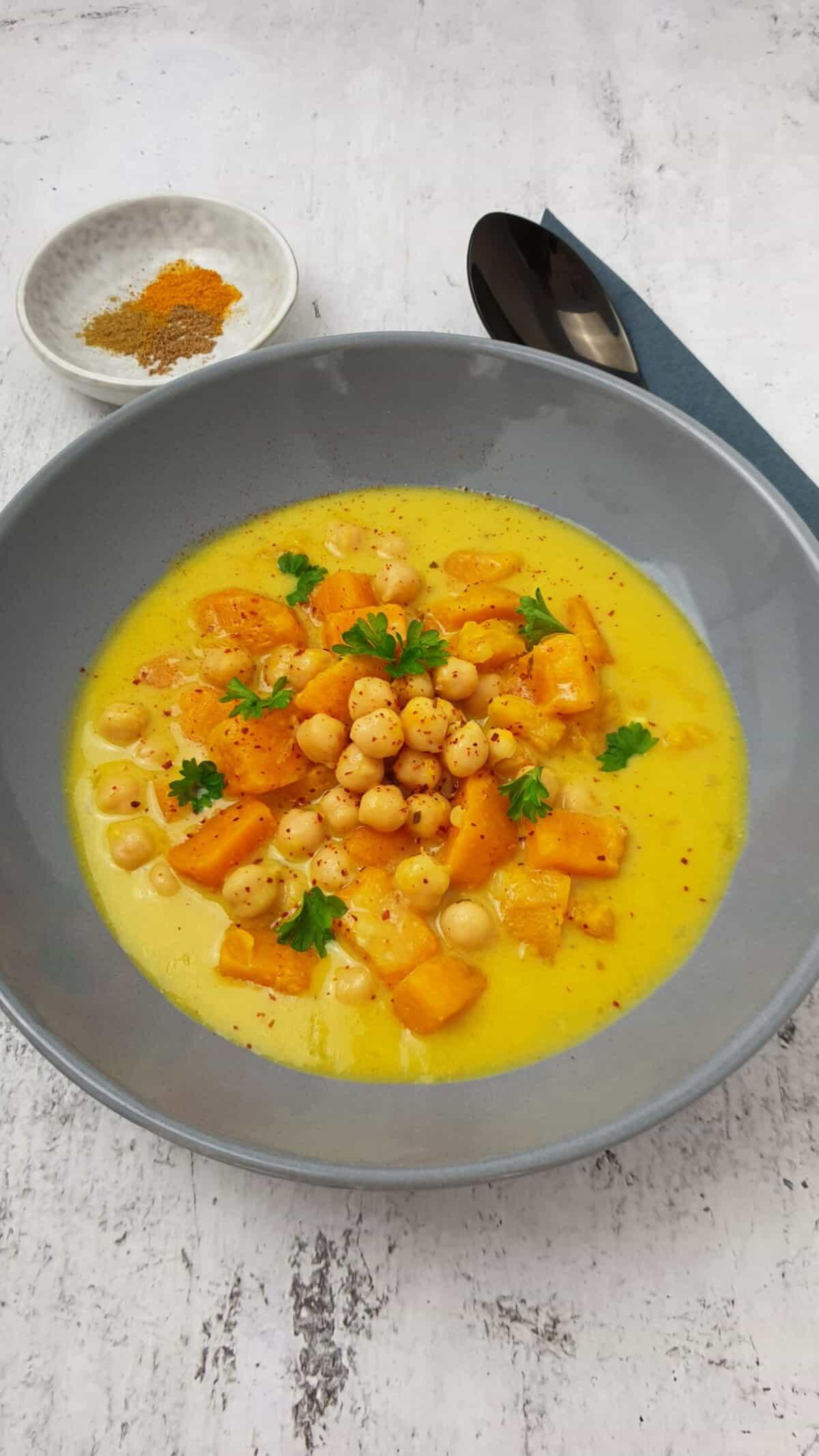 Süßkartoffel-Suppe mit Kichererbsen und Kokosmilch in einer grauen Schale angerichtet.