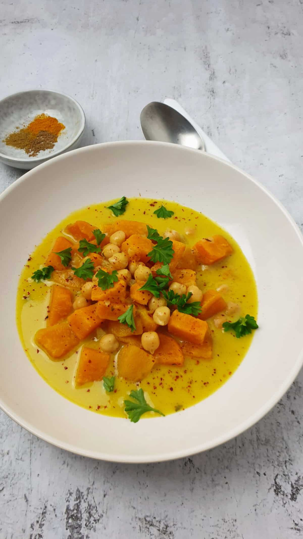 Süßkartoffel-Suppe mit Kichererbsen und Kokosmilch in einer weißen Schale angerichtet.