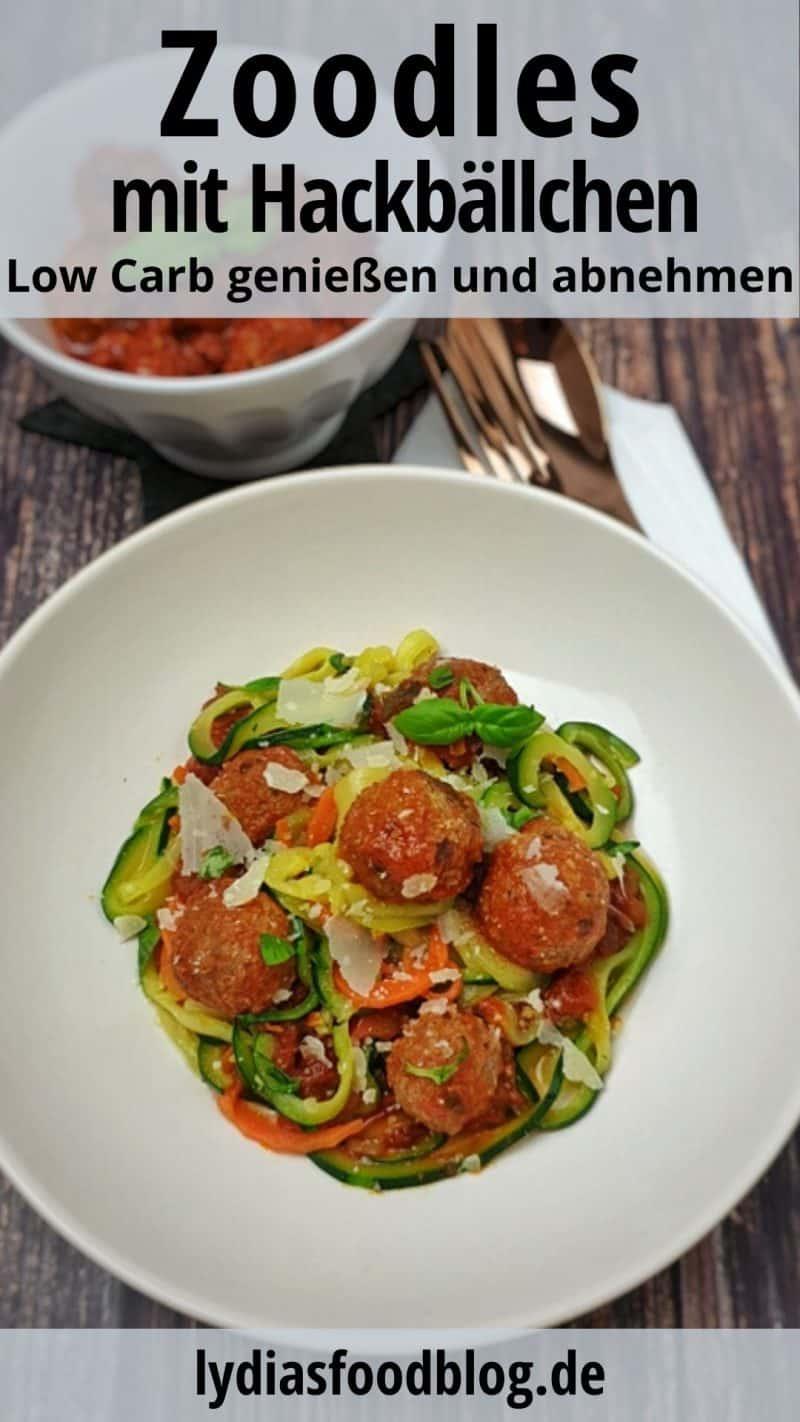 Zoodles mit Hackbällchen und Tomatensoße angerichtet in einer weißen Schale mit Parmesan bestreut.