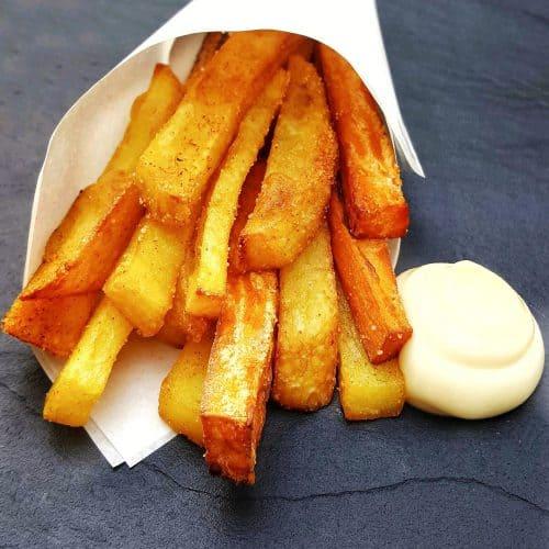 Selbst gemachte 2erlei Pommes aus Kartoffel und Süßkartoffel in einer Papiertüte mit Mayonnaise auf einer Schieferplatte serviert.