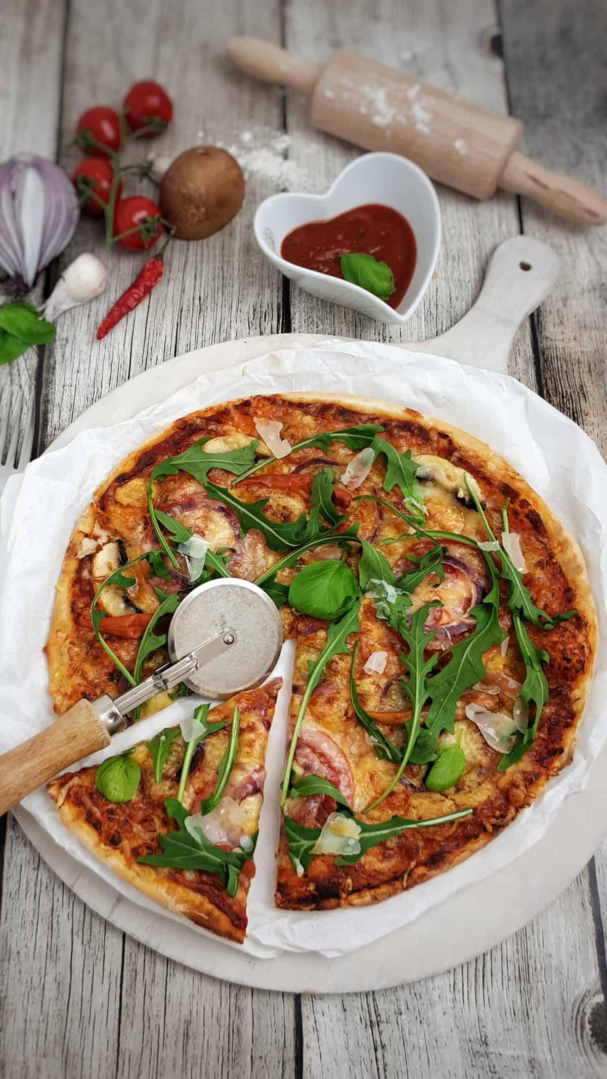 Auf einem mit Backpapier belegtem runden Brett eine Dinkel Pizza mit Champignons, Rucola, Zwiebeln und Käse.