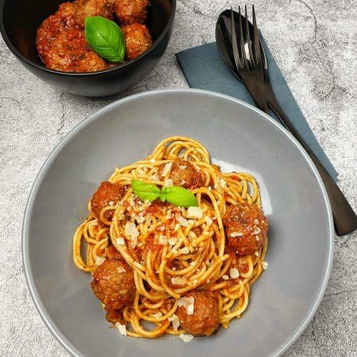 Italinische Hackbällchen mit Spaghetti angerichtet in einer grauen Schale mit Parmesan und Basilikum garniert.