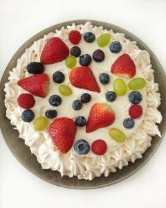 Eine Pavlova mit Sahne Creme und Früchten.