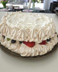 Eine zweistöckige Baiser Torte mit Füllung aus einer Sahne und Früchten.