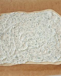 Ein Flammkuchenteig mit Crème fraîche bestrichen auf einem Backpapier.