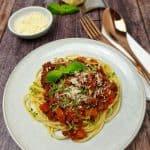 Auf einem weißen Teller dekorativ angerichtete Spaghetti mit Blitz Bolognese garniert mit einem Basilikum Blatt und Parmesan. Im Hintergrund sieht man ein Stück Parmesan sowie eine kleine Schale mit geriebenem Parmesan.