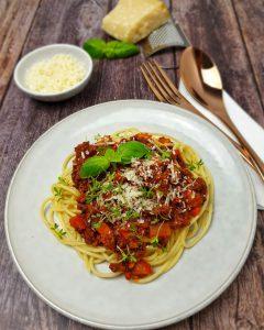 Auf einem weißen Teller dekorativ angerichtete Spaghetti mit tomatiger Bolognesesoße garniert mit einem Basilikumblatt und Parmesan