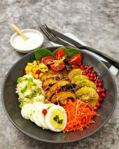 eine Budha Bowl mit Couscous, Gemüse und Früchten, vegetarisch