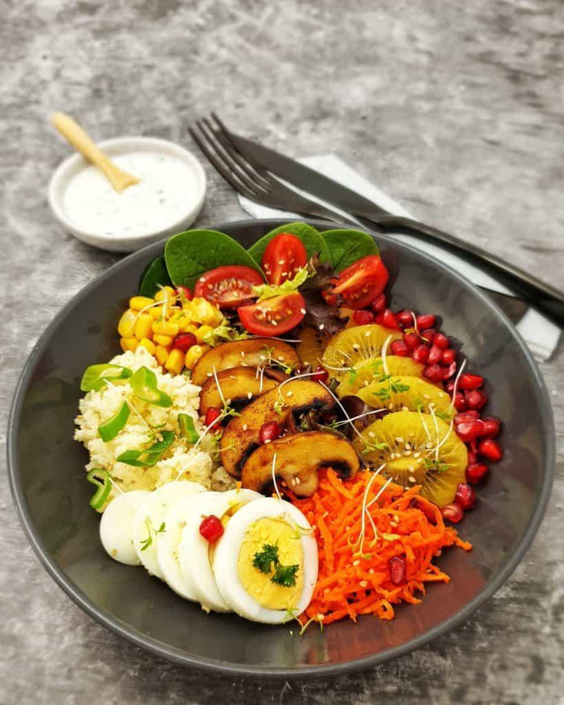 Buddha Bowl mit Couscous, Gemüse und Früchten angerichtet in einer braunen Schale.