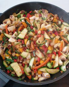 Klein geschnittenes Gemüse in Öl in einer Pfanne gebraten.