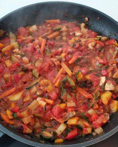 Gebratenes Gemüe mit gehackten Tomaten kocht in einer schwarzen Pfanne.