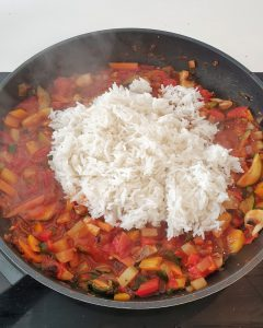Vorgekochter Reis kommt in die Gemüse-Tomaten Mischung.