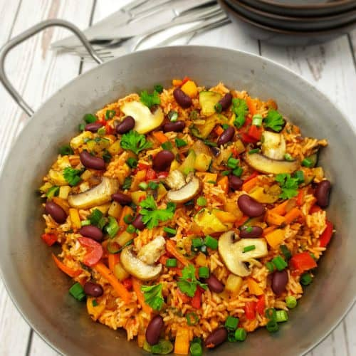 Gemüse-Reis-Pfanne in einer gußeisernen Pfanne angerichtet, mit Petersilie bestreut.