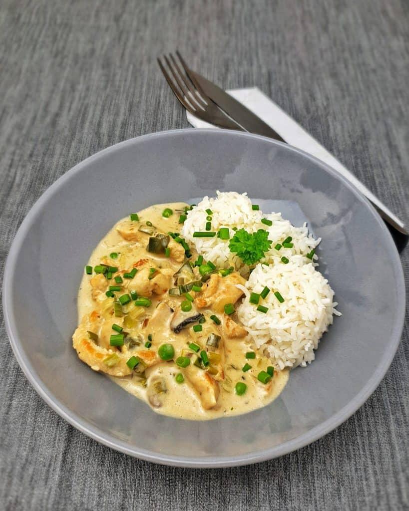 Hähnchengeschnetzeltes mit Reis in einer hale angerichtet und mit Petersilie und Schnittlauch bestreut.