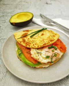 Pfannkuchen Burger mit Lachs und Avocado auf einem grauen Teller angerichtet und mit Dill bestreut.