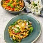 Italienischer Nudelsalat mit Pesto, Rucola und Tomaten angerichtet auf einem ovalen, blauen Teller