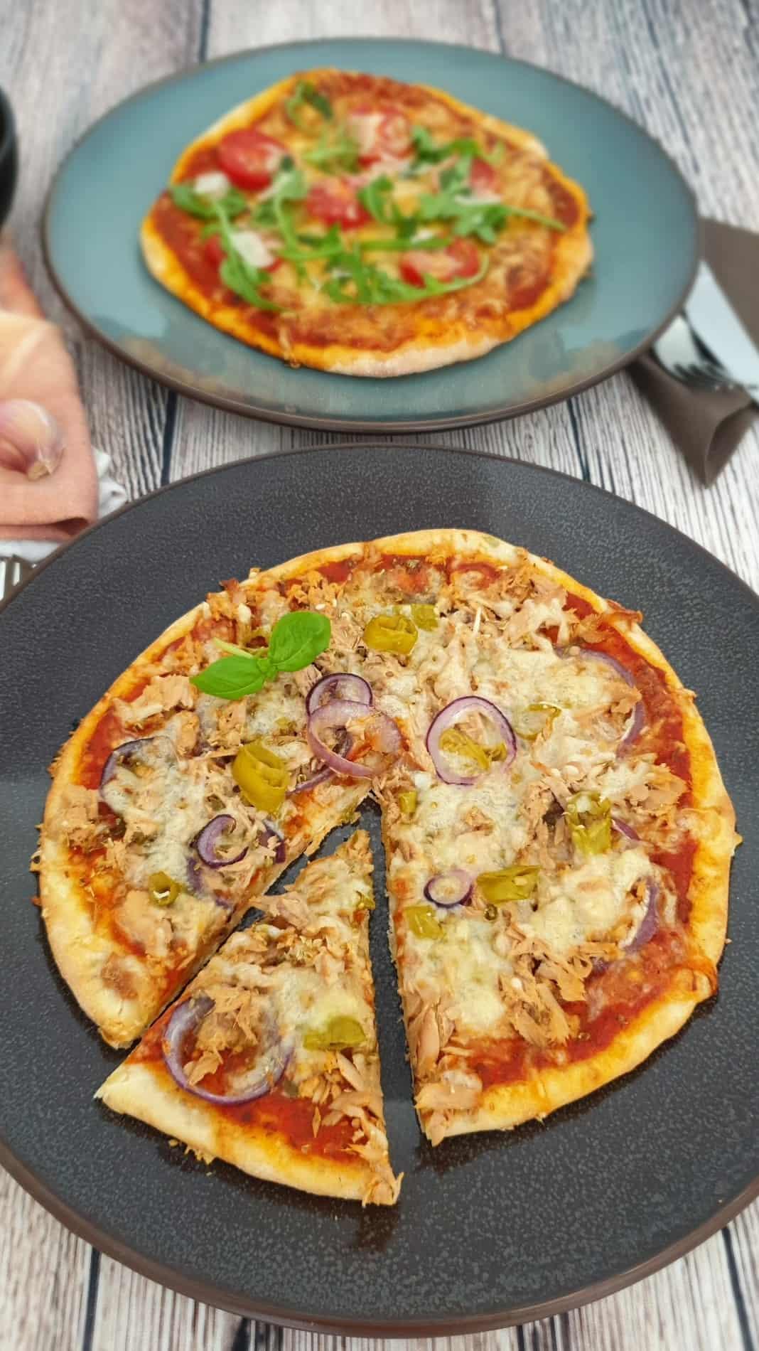 Auf einem dunklen großen Teller eine Dinkel Pizza mit Thunfisch, Zwiebeln und Käse. Im Hintergrund Deko.