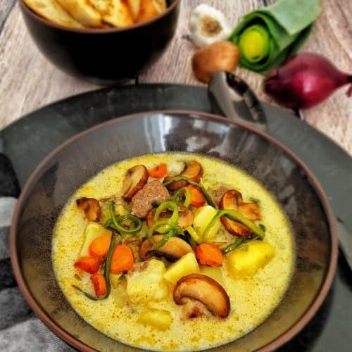 Käse-Lauch-Suppe mit Hackfleischbällchen in einer braunen Schale angerichtet. Im Hintergrund Deko.