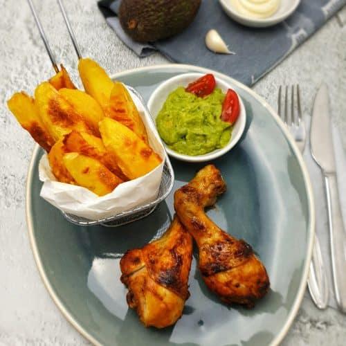 Knusprige Hähnchenunterkeulen mit Kartoffeln aus dem Backofen auf einer blauen ovalen Servierplatte.