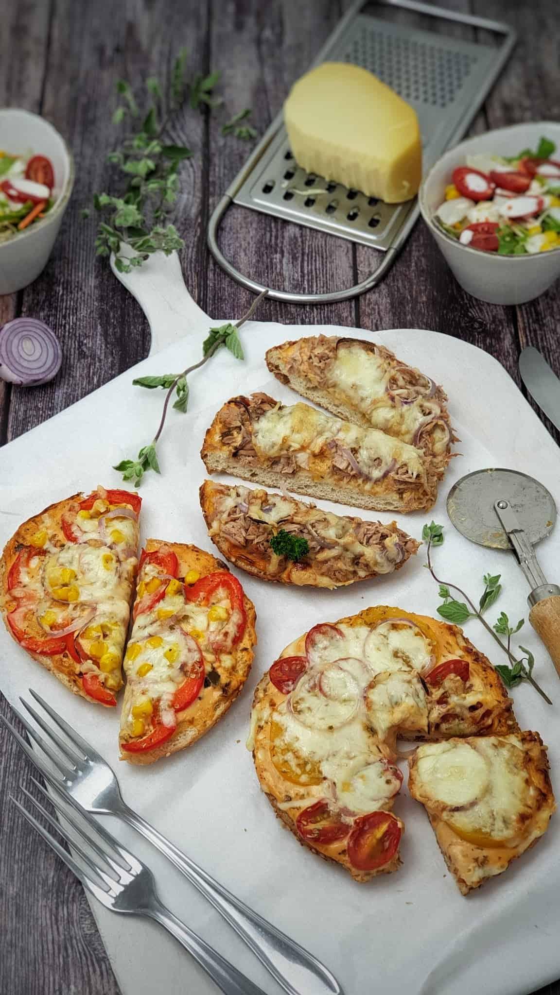 Auf einem großen Servierbrett 3 kleine Mini Fladenbrot Pizza mit verschiedenem Belag.
