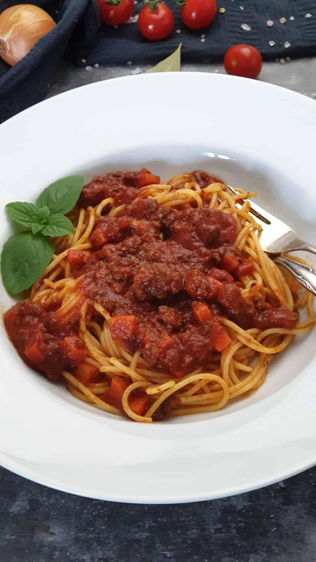 Auf einem hellen Teller angerichtet Blitz Bolognese mit Basilikum.