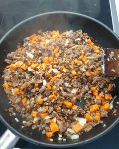 In einer Pfanne angebratenes Hackfleisch mit Möhren und Sellerie-Würfel.