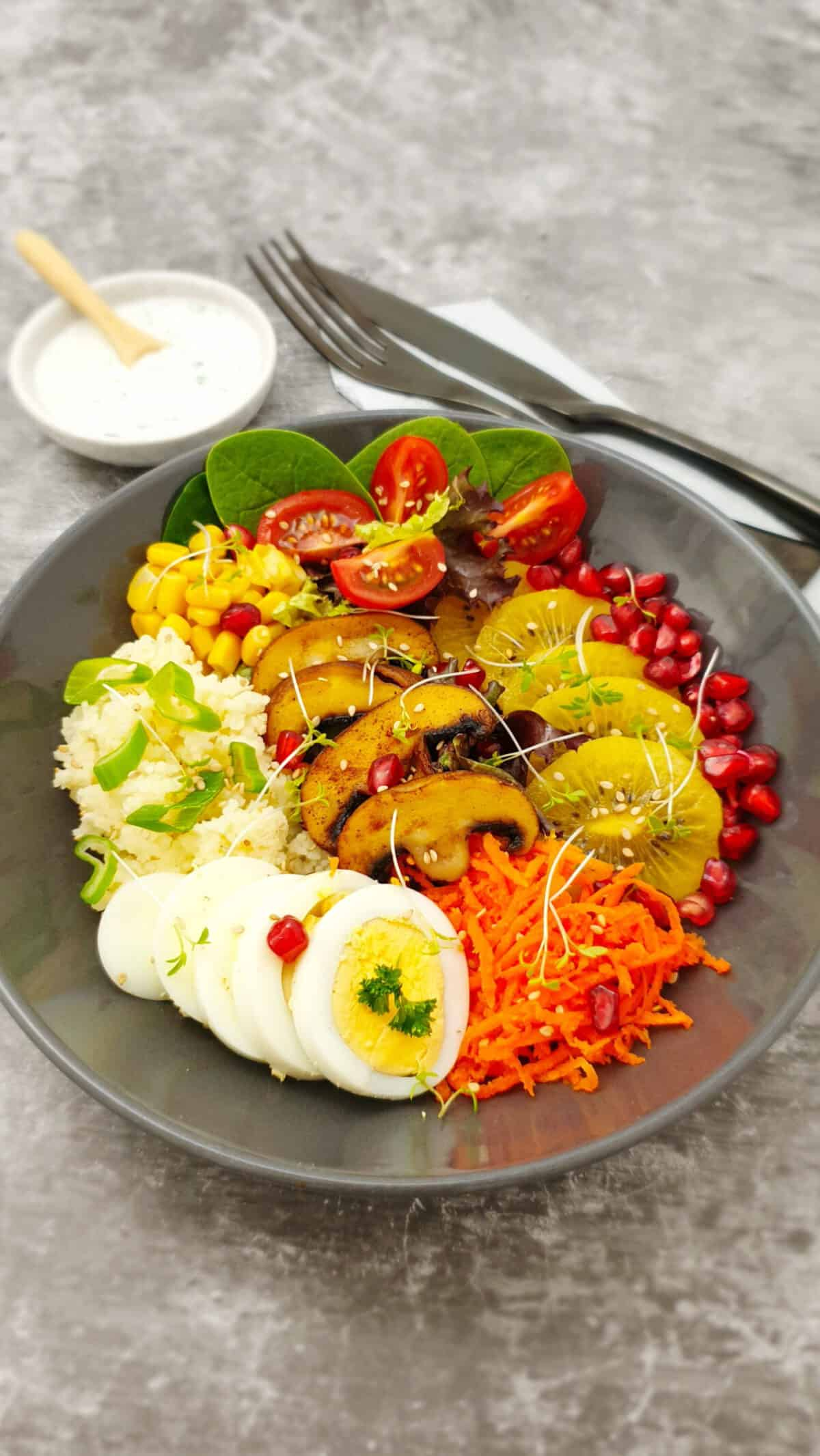 In einer braunen Schale eine Buddha Bowl mit Couscous, Gemüse, Obst und Ei.
