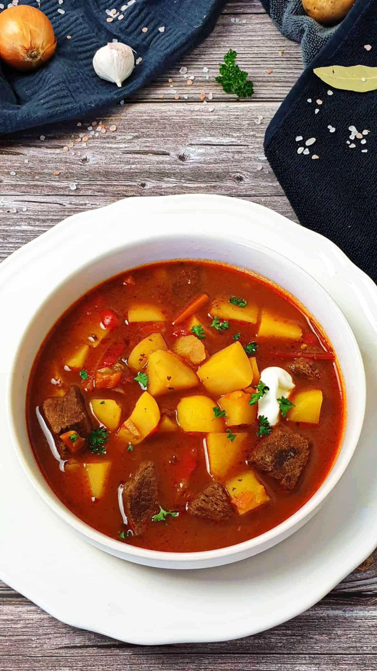 In einer weißen Schale Gulaschsuppe mit Rindfleisch, Paprika und Kartoffeln. Im Hintergrund Deko.