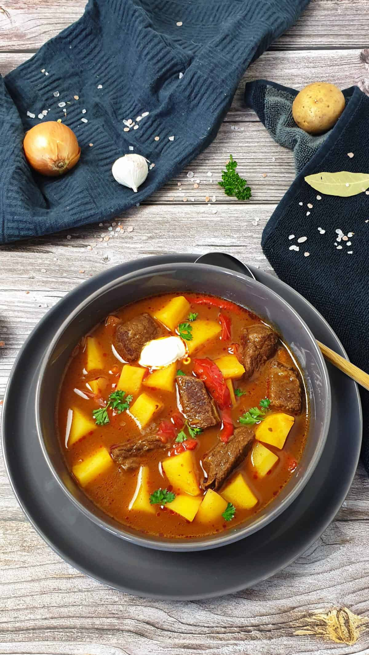 In einer grauen Schale Gulaschsuppe mit Rindfleisch, Paprika und Kartoffeln. Im Hintergrund Deko.