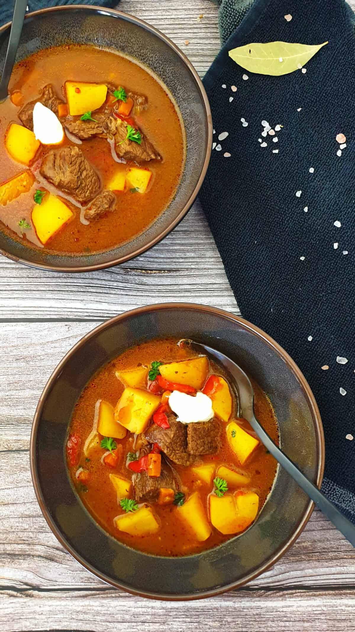 In zwei braunen Schalen Gulaschsuppe mit Rindfleisch, Paprika und Kartoffeln. Im Hintergrund Deko.
