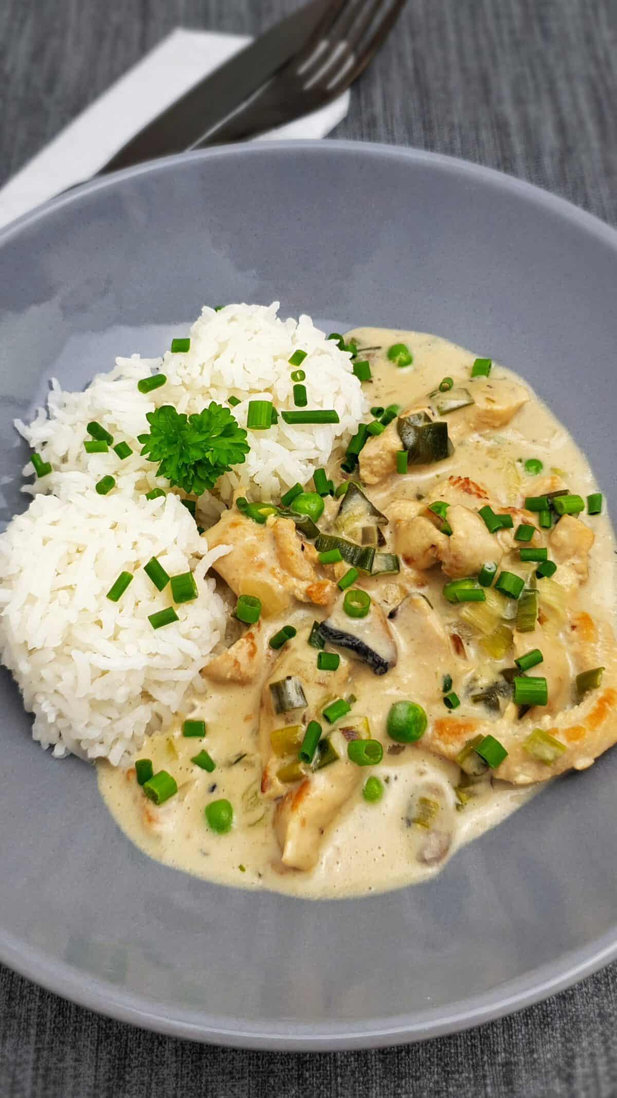 In einer hellgrauen Schale angerichtet Hähnchengeschnetzeltes mit Reis und Erbsen, Mit Petersilie bestreut. Daneben Besteck.