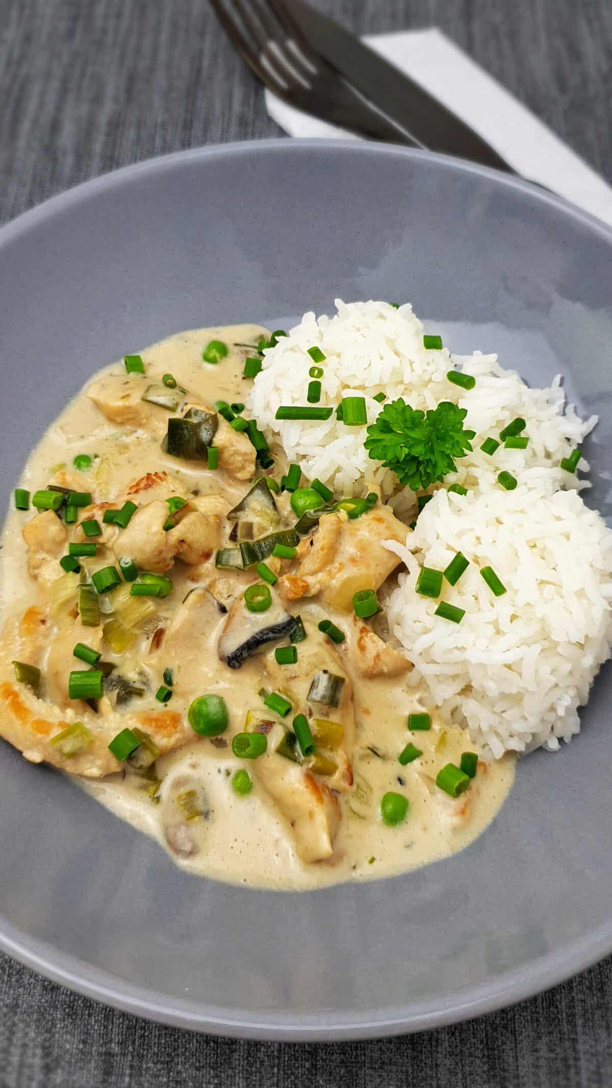 In einer hellgrauen Schale angerichtet Hähnchen-Geschnetzeltes mit Reis und Erbsen, Mit Petersilie bestreut. Daneben Besteck.